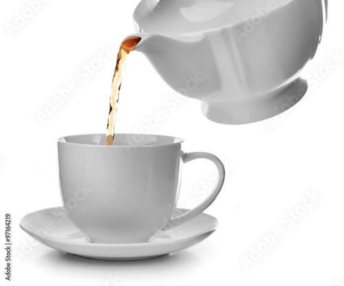 Poster Café en grains Tea flows from a teapot in a cup isolated on white background