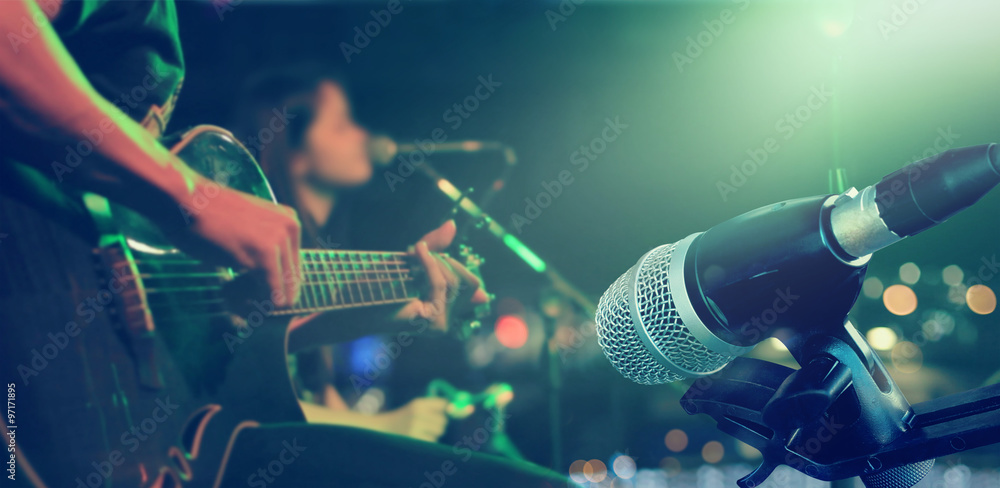 Guitarist on stage with microphone for background, soft and blur concept