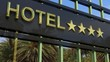 Metallic glass hotel sign board with four golden stars, text and palm trees as background.