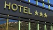 Metallic hotel sign board with three golden stars and island with seascape as background.