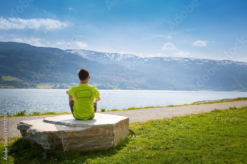 a man sitting on a stone