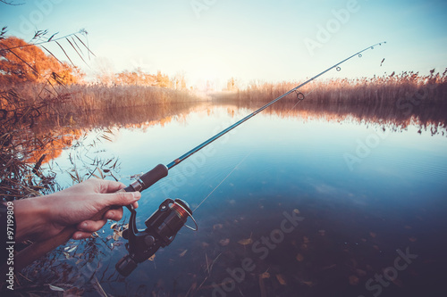 Printed kitchen splashbacks Fishing hand with spinning and reel on the evening summer lake