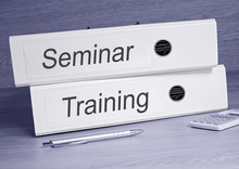 Seminar And Training - Two White Binders With Text On Desk In The Office