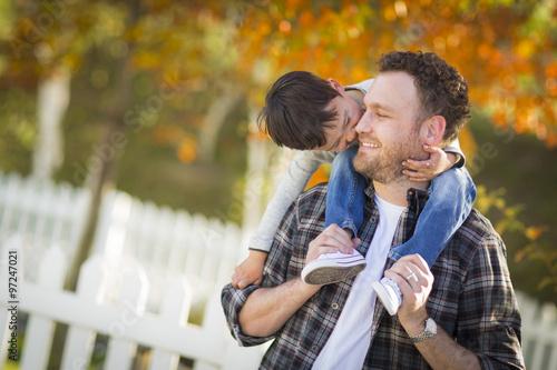 Fotografie, Obraz  Mixed Race Boy Riding Piggyback on Shoulders of Caucasian Father