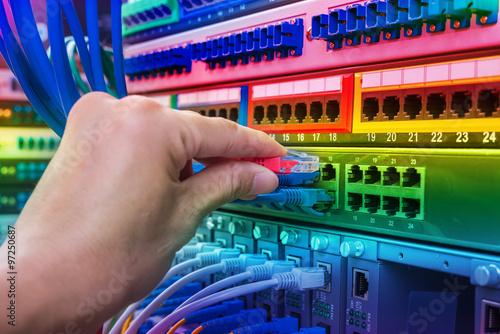 Fotografie, Obraz  man working in network server room with fiber optic hub for digi