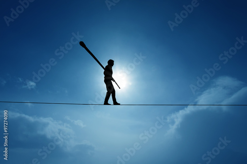 Fotografía Concept of risk taking and challenge highline walker in blue sky
