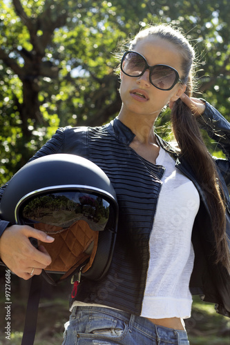 Fotobehang Fiets Beautiful fashion woman in black leather jacket with helmet on road. Phuket island, Thailand