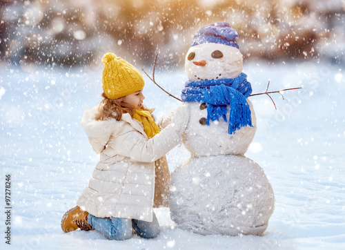 Photo  girl playing with a snowman