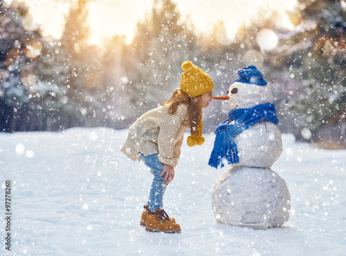 Obraz girl playing with a snowman - fototapety do salonu