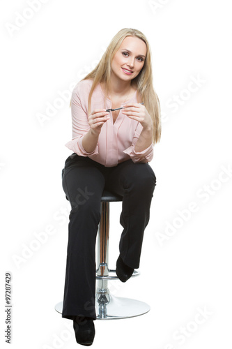 Valokuva  Elegant beautiful woman sitting on a contemporary metal bar stool