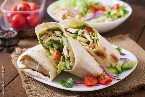 Fotografie, Obraz  Fresh tortilla wraps with chicken and fresh vegetables on plate