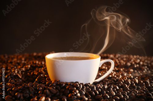 Wall Murals Cafe Cup of hot coffee and coffee beans closeup