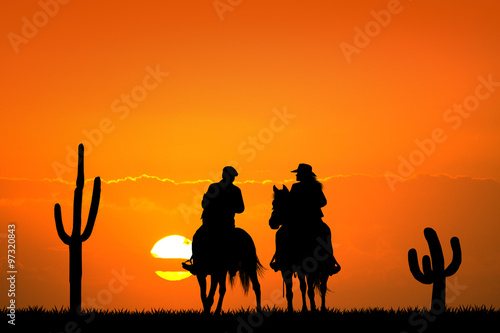 Photo  people on horseback at sunset