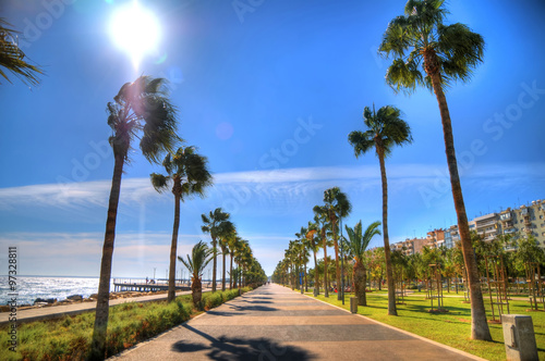 HDR image of the sun over the promenade alley near coast line of Limassol, Cyprus on a sunny day on the background of a clear blue sky.