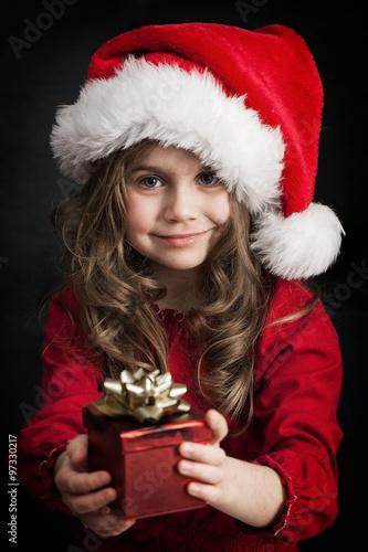 Dziewczynka w czapce świętego Mikołaja z prezentem Poster