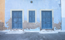 Mediterranean Style Exterior. Blue Wooden Doors And Window Shutters, Old Painted Wall On A Greek Island