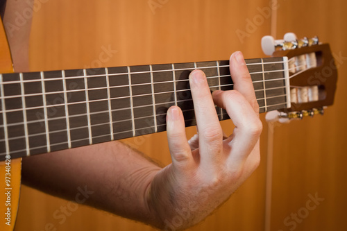Fotografering  Guitarist hand playing acoustic guitar