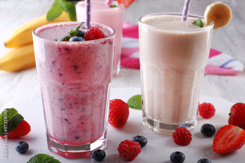 Milkshakes with berries on light wooden background, close-up