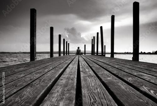 Steg mit Frau und Wolken Fototapet