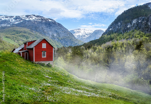 Red wooden cottage in the foggy valley. Green grass, white flowers. Stone snowy mountains. Stalheim, Norway. Mist. #97375485