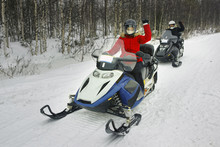 Woman And Man Driving Snowmobile In Ruka Of Lapland