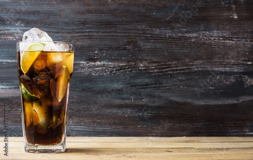 Photo  Glass of cola with ice and lime on the rustic background