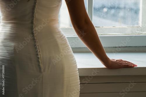 Stampa su Tela Невеста в белом платье стоит у окна спиной к зрителю