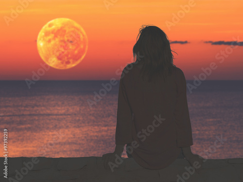 Girl watching the ocean / sea horizon with a Moon rise.