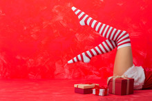 Woman In Christmas Socks Laying On The Floor Next To The Gifts
