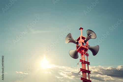 Foto  Horn speaker for public relations sign symbol, vintage color - sun with blue sky