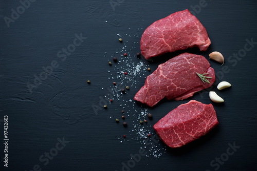 Fotografering  Fresh black angus beefsteaks, black wooden background, copyspace