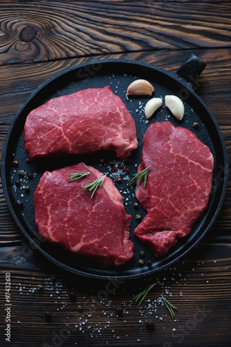 Photo  Frying pan with fresh uncooked marbled beef steaks