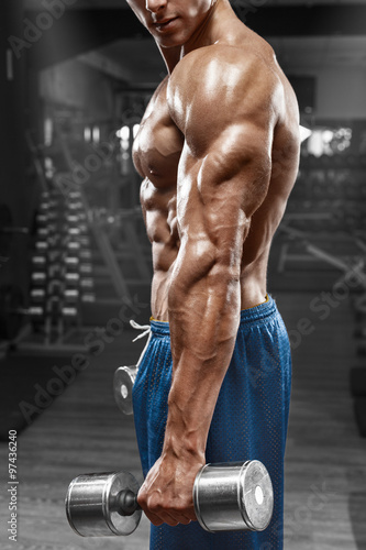 obraz dibond Muscular man posing in gym, showing triceps. Strong male naked torso abs, working out, focus on the hand