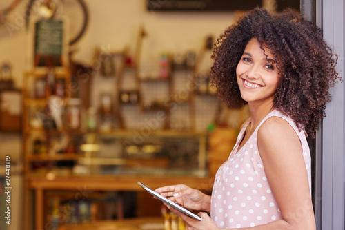 Mixed race woman standing in the door of her coffee shop with a