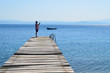Man on an old wooden pier taking photo with his phone