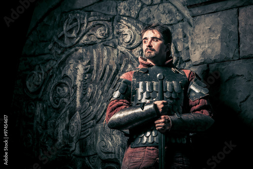 Fotografia Medieval knight with the sword on the ancient castle background