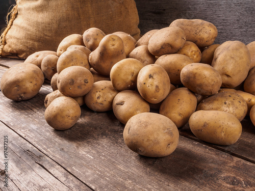 Potatoes From Bag Lying On Wooden Boards
