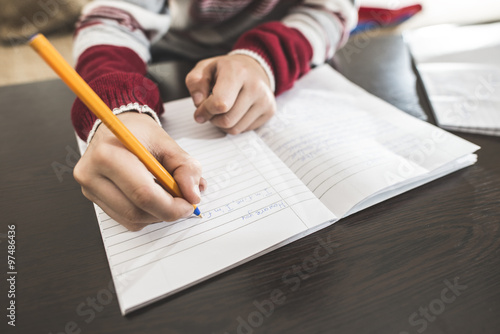 Fotografie, Tablou  Child write in a notebook.