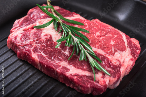 Fotografering  Raw marbled meat steak Ribeye on grill pan on dark wooden background
