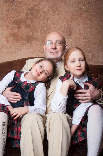 Photo  Дед и две внучки обнимаются и улыбаются в костюмах