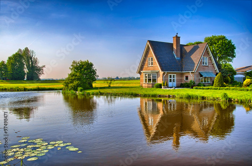 Red bricks house in countryside near the lake with mirror reflec Fototapeta