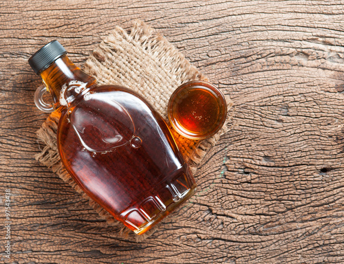 Fotografia maple syrup in glass bottle on wooden table