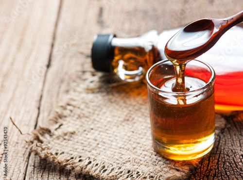 maple syrup in glass bottle on wooden table Canvas