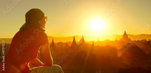 female traveler watching sunset over ancient temples at Bagan, Myanmar.