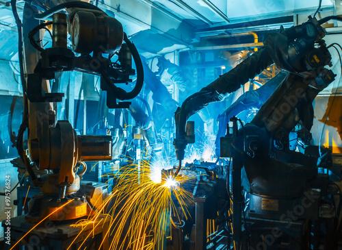 Obraz Team welding Robot movement Industrial automotive part in factory - fototapety do salonu