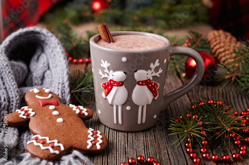 Spoed Foto op Canvas Chocolade Cup of hot chocolate or cocoa with two cute deer, cinnamon and gingerbread man cookie in new year tree decorations frame on vintage wooden table background. Homemade traditional celebration recipe