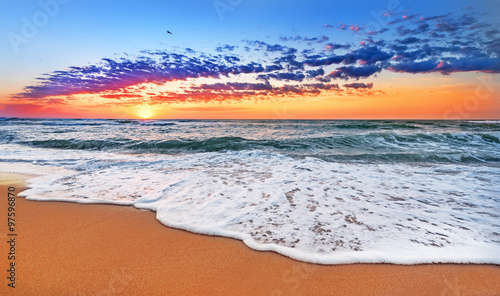 Foto op Canvas Strand Colorful ocean beach sunrise.
