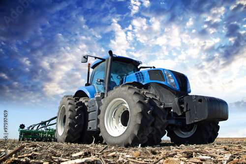 Blue tractor working on the farm плакат