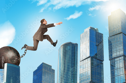 Photo Man with iron ballast hopping over town