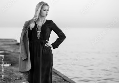 High fashion photo of elegant woman in black long dress and styl